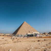 A wide angle shot of an Egyptian pyramid under a clear blue sky